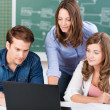 Teacher working with two teenage students — Stock Photo
