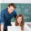Young man helping a teenage girl in class — Stock Photo