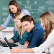 Young teenage students working in class — Stock Photo