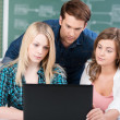 Three students working at a laptop — Stock Photo