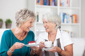 Two elderly ladies enjoy a cup of tea — Stock Photo