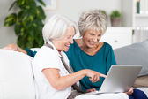 Two senior women surfing the internet — Stock Photo