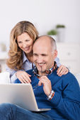 Couple smiling as they surf the internet — Stock Photo