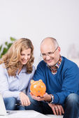 Couple gazing at their piggy bank with a smile — ストック写真