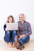 Husband and wide relaxing with a laptop — Stock Photo