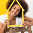 Smiling woman decorating her new house — Stock Photo #38562837