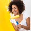 Playful African American woman painting — Stock Photo