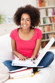 Cheerful female student sitting on the sofa — Stock Photo