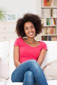 Frau sitzt auf einem weißen sofa im wohnzimmer — Stockfoto