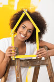 Smiling woman decorating her new house — Stock Photo