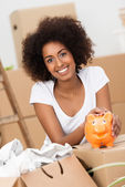 Smiling young woman caressing her piggy bank — Stock Photo