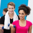 Multiethnic couple working out with dumbbells — Stock Photo #38613711