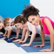 Group of fit young people doing push ups — Stock Photo #38619741