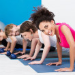 Group of fit young people doing push ups — Stock Photo