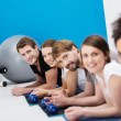 Line of young friends exercising in the gym — Stock Photo