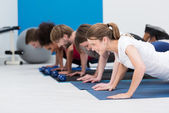 Diverse young people working out in a gym — Stock Photo