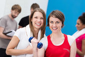 Young woman lifting weights aided by a friend — Stock Photo