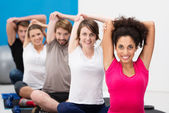 Group of fit young friends exercising at the gym — Stock Photo