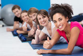 Vivacious young people working out in the gym — Stock Photo