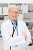 Friendly elderly male doctor in his office — Stock Photo