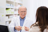 Helpful pharmacist dispensing medicine — Stock Photo