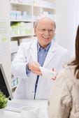 Friendly pharmacist dispensing medicine — Stock Photo