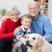 Happy little boy with his elderly grandparents — Stock Photo