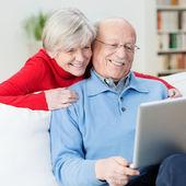 Amused senior couple using a laptop computer — Stock Photo