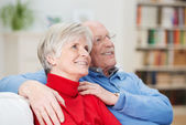 Happy senior couple sitting watching something — Stock Photo