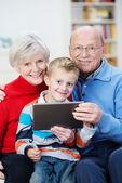 Elderly grandparents with their little grandson — Stock Photo