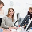 Smiling young businesswoman in a busy office — Stock Photo #40764551