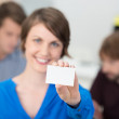 Friendly businesswoman holding up a blank card — Stock Photo #40767631