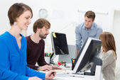Young businesspeople working in a busy office — Stock Photo