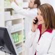 Pretty young pharmacist chatting on the phone — Stock Photo #40843893