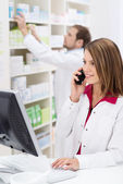 Pretty young pharmacist chatting on the phone — Stock Photo