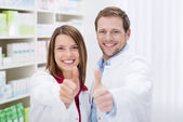Motivated pharmacists giving a thumbs up — Stock Photo
