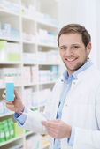 Happy pharmacist holding a blank box of medication — Stock Photo