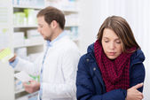 Sick woman waiting in a pharmacy — Stock Photo