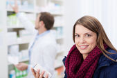 Smiling beautiful woman waiting in a pharmacy — Stock Photo