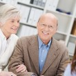 Smiling retired couple in a business meeting — Stock Photo