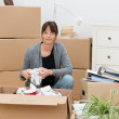 Woman moving house packing her belongings — Stock Photo