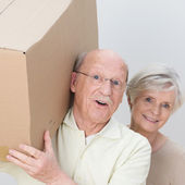 Energetic senior couple moving home — Stock Photo
