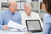 Elderly couple in a meeting with an adviser — Stock Photo
