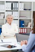 Senior woman attending a meeting in an office — Stock Photo