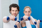 Fit young couple working out at the gym — Stock Photo