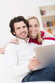 Young couple sharing a laptop at home — Stock Photo