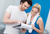 Young woman talking to her fitness trainer — Stock Photo
