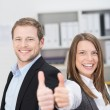 Motivated businessman and woman giving a thumbs up — Stock Photo