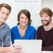 Confident business team grouped around a laptop — Stockfoto