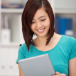 Young Asian woman smiling as she reads her tablet — Stock Photo #42488349